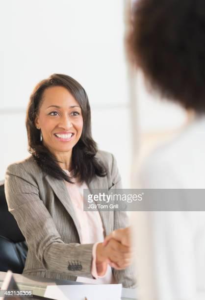 African American businesswomen shaking hands