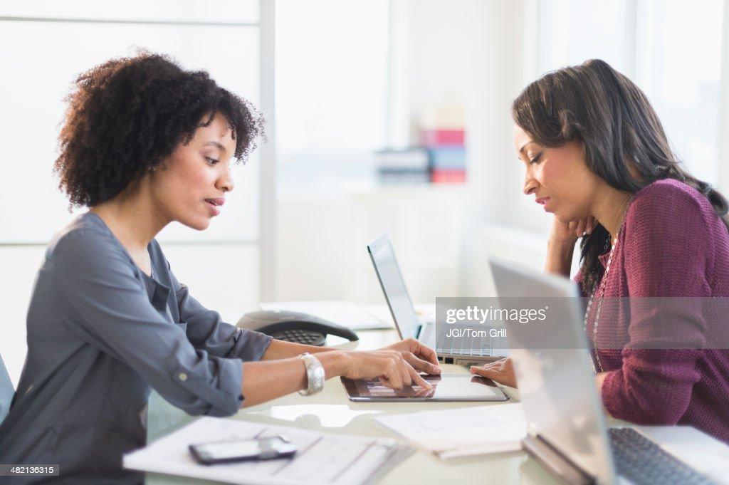 African American businesswomen talking in meeting : Stock Photo