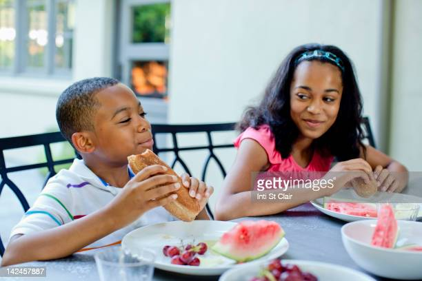 African American children eating lunch outdoors