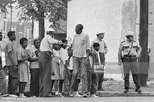 African American children participating in a Civil Rights protests wait for a police van to take them to jail in Birmingham Alabama