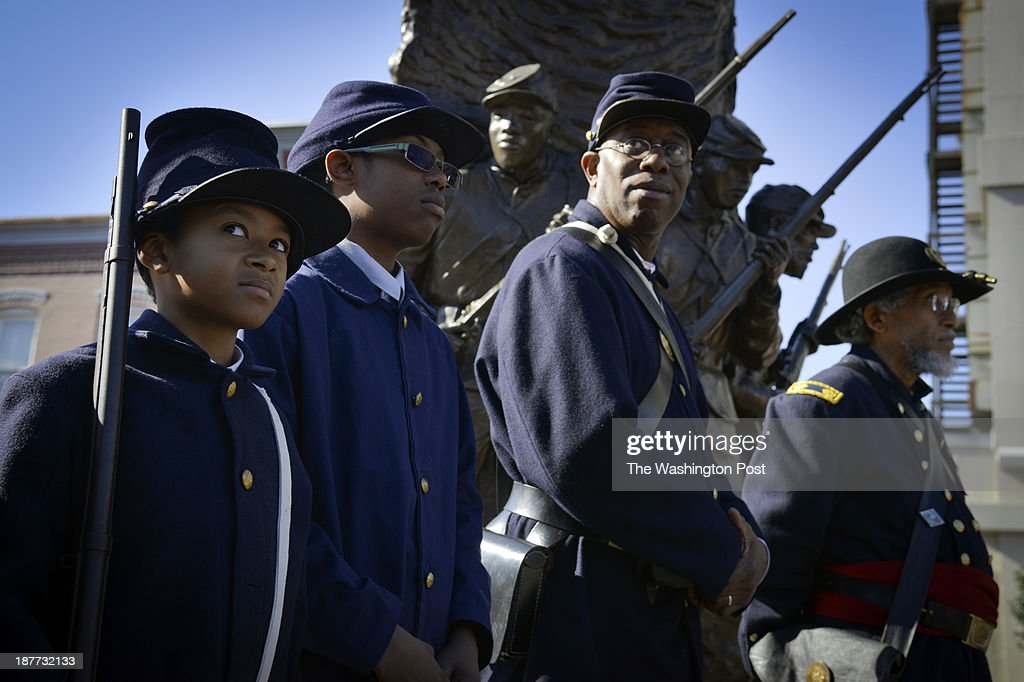 African American Civil War re-enactors - from left, Wyatt Harris, 8, Nile Smith, 13, Bryan Cheeseboro, and Asa Gordon - stand near the African American Civil War Memorial as a few original Tuskeegee Airmen with DC connections are commemorated on Monday, November 11, 2013, in Washington, DC. At the commemoration, Congresswoman Eleanor Holmes Norton honored two D.C. residents, Major Louis Anderson and William Fauntroy. Anderson received a replica of the Congressional Medal of Honor.