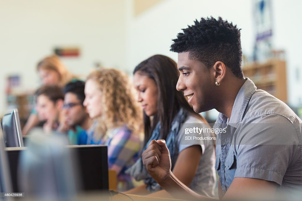 African American college student smiling while using computer in library : Stock Photo