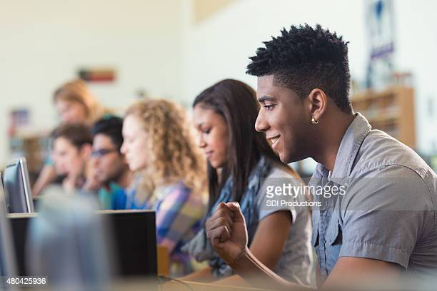 African American college student smiling while using computer in library