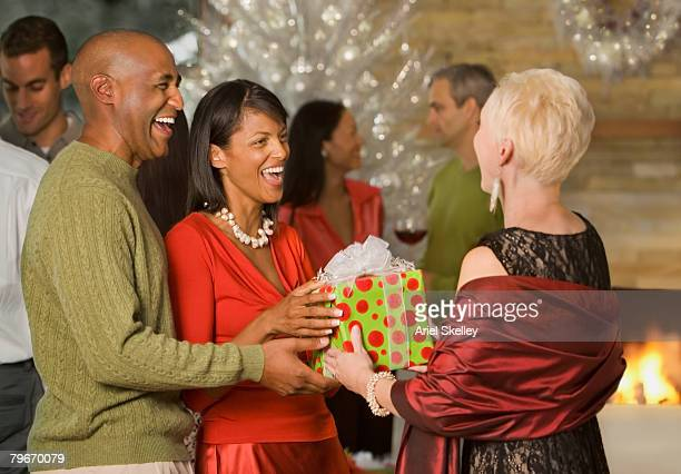 African American couple giving gift at party