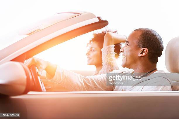 African American couple in convertible car.