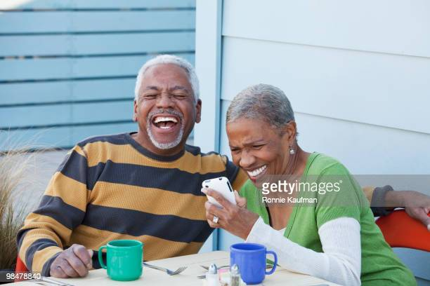 African American couple laughing at photographs