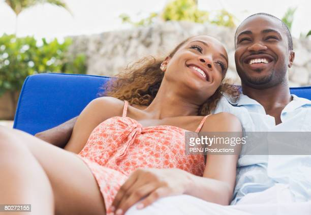 African American couple laying on lounge chair