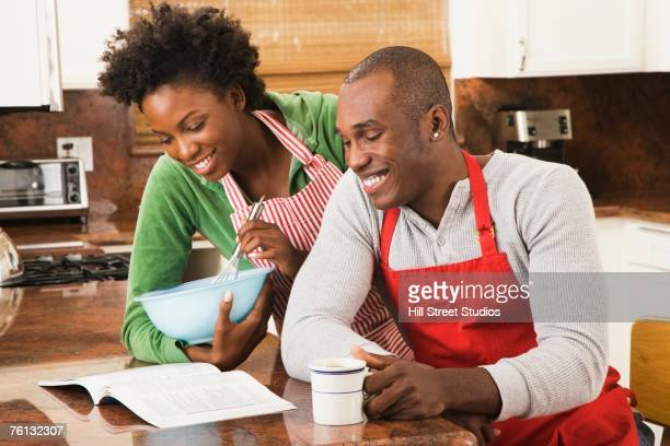 African American couple reading cookbook