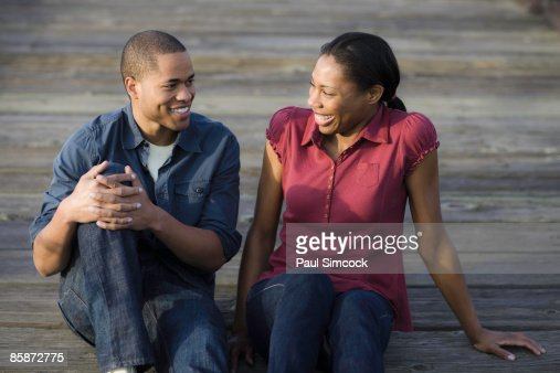 African American Couple Sitting On Boardwalk