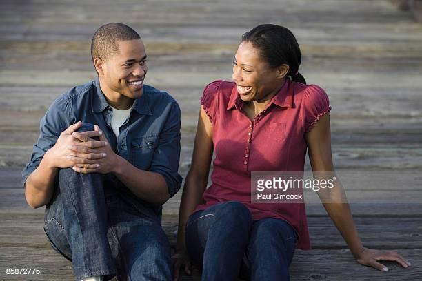 African American Couple Sitting On Boardwalk