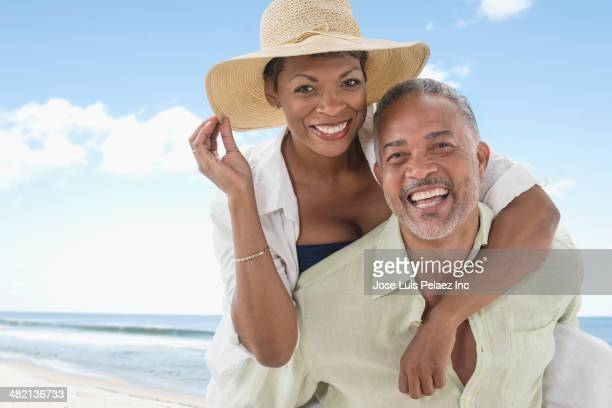 African American couple smiling on beach