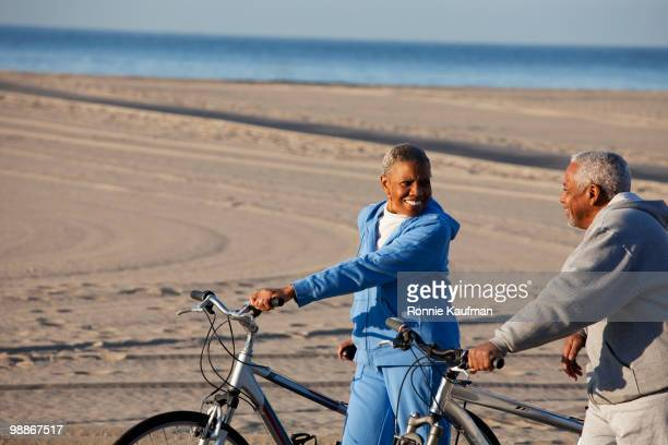 African American couple standing with bicycles on beach