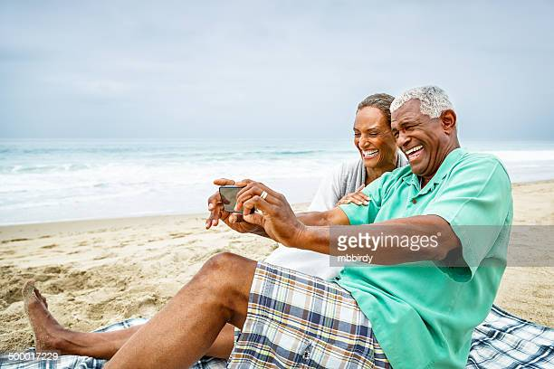 African American couple taking selfie at beach