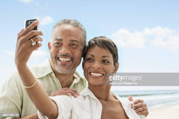 African American couple taking self-portrait on beach