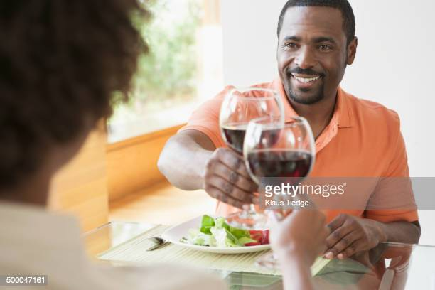 African American couple toasting each other at dinner