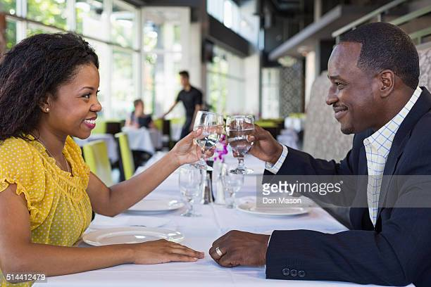 African American couple toasting each other in restaurant