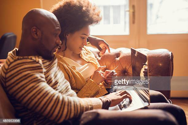 African American couple using laptop for online shopping at home.