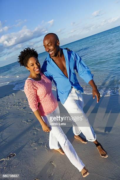 African American couple walking on beach