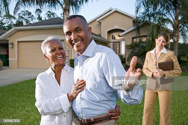 African American couple with real estate agent outside house