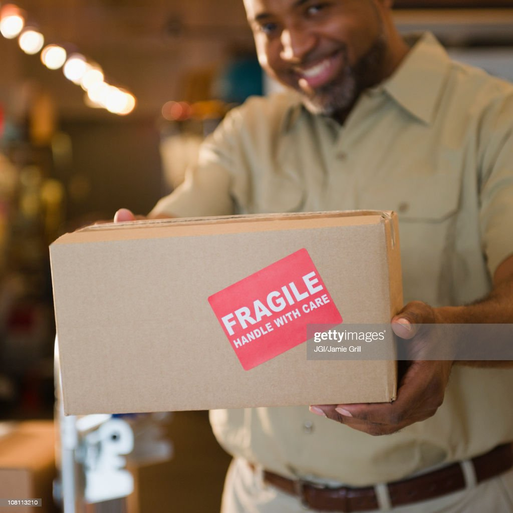 African American deliveryman holding out box with 'fragile' sticker : Stock Photo