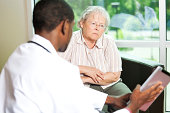 African american doctor consulting with a senior woman
