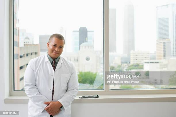 African American doctor standing near hospital window