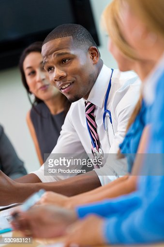 African American doctor talking to colleagues in hospital staff meeting