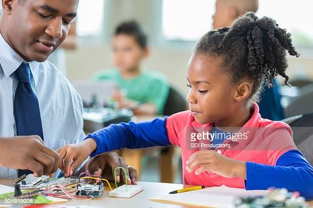 African American elementary age little girl using robotics kit