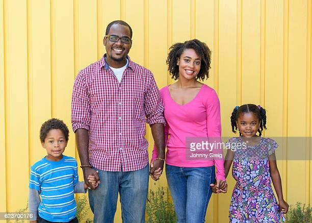 African American family against yellow background, smiling