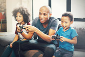 African American family at home sitting in sofa couch and playing console video games together.African American family at home sitting in sofa couch and playing console video games together