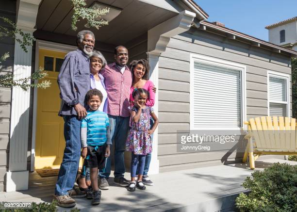 African American family by front door, smiling