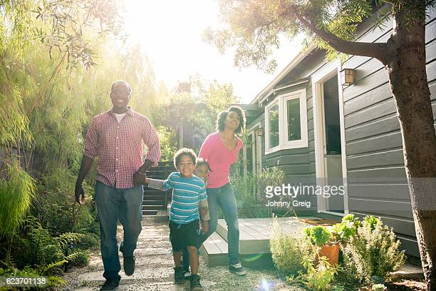 African American family holding hands in garden