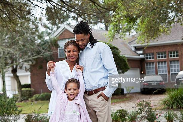 African American family in front of house
