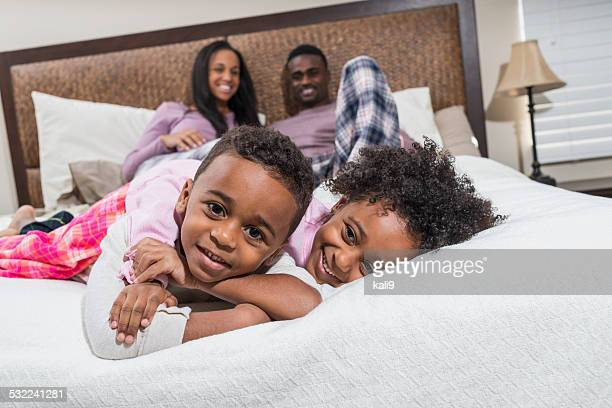 African American family lying on a bed