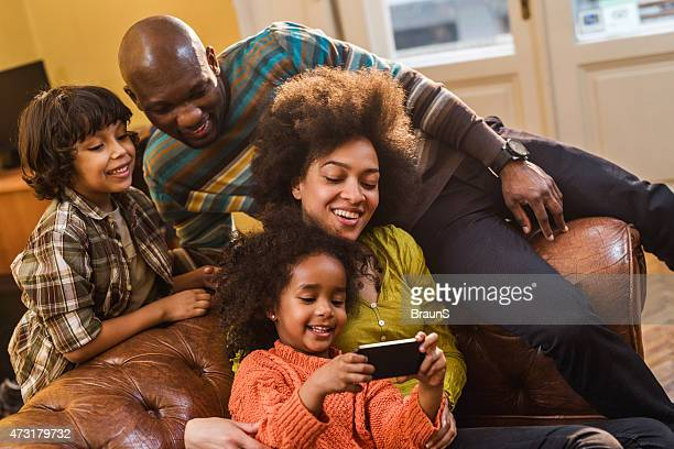 African American family relaxing at home and using cell phone.