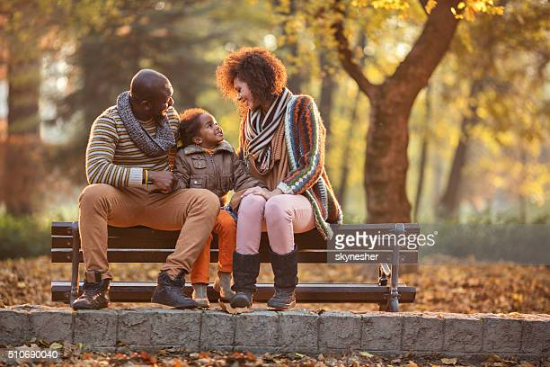 African American family relaxing on bench in the autumn park.