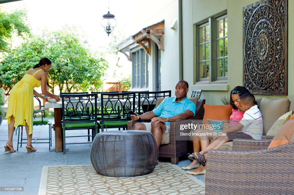 African American family relaxing on patio : Stock Photo