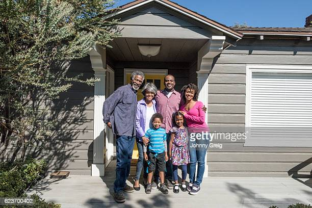 African American family standing on driveway outside house