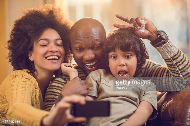 African American family taking a funny selfie with mobile phone.