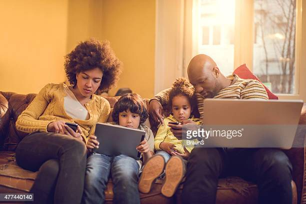 African American family using wireless technology at home.