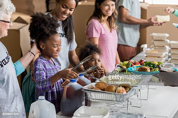 African American family volunteers at soup kitchen