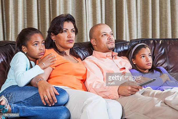 African American family watching TV, on sofa together