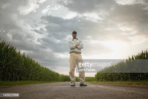 African American farmer standing on road through crops