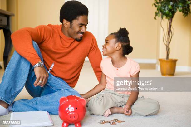 African American father and daughter counting piggy bank coins