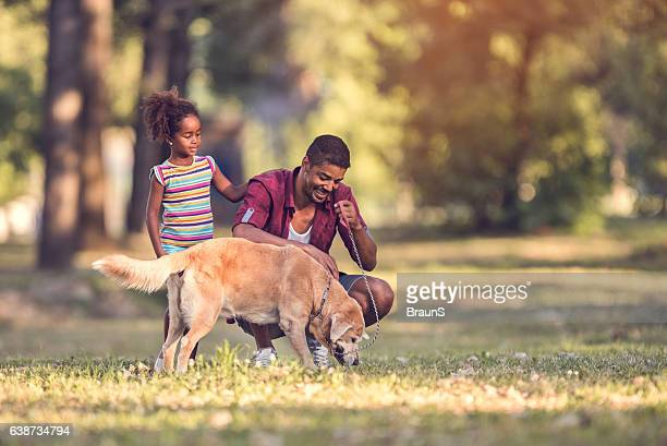 African American father and daughter enjoying with their dog outdoors.