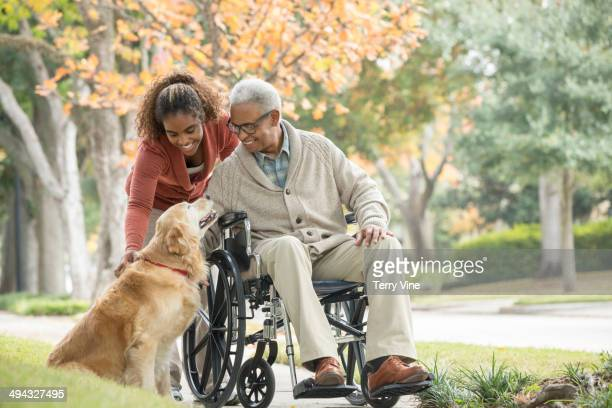 African American father and daughter petting dog