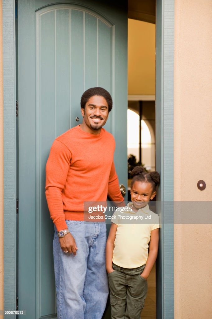 African American father and daughter smiling in doorway