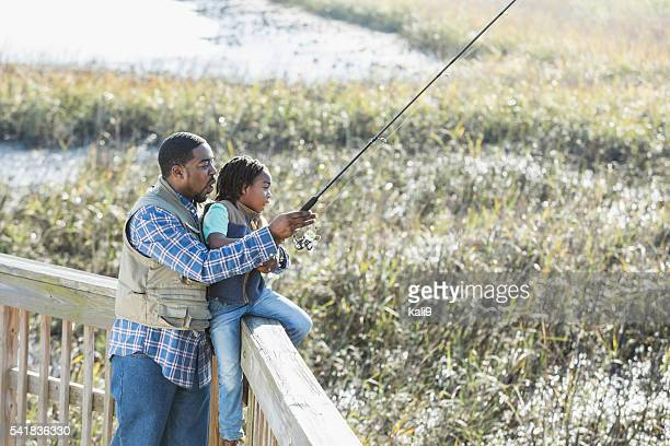 African American father and son fishing together
