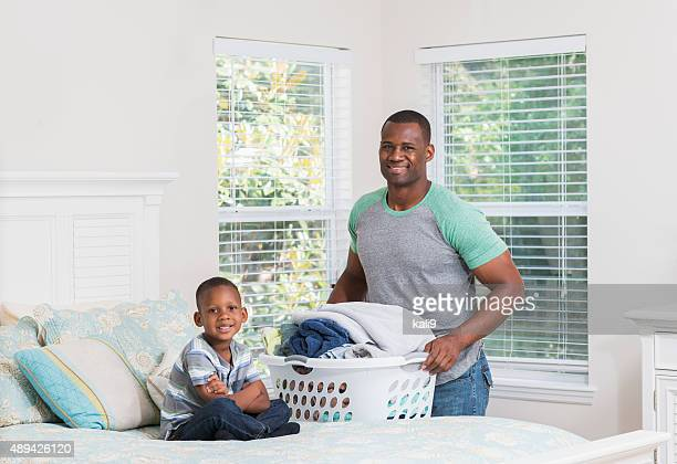 African American father and son, laundry basket on bed