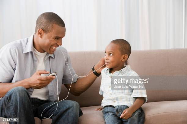 African American father and son listening to mp3 player